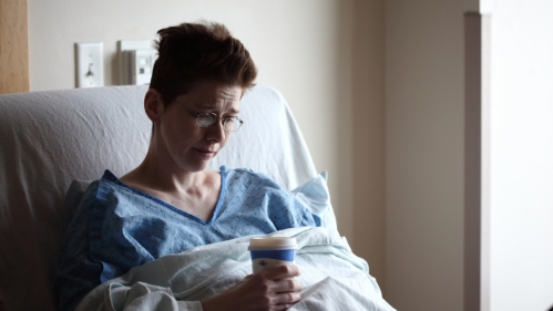 white woman with short hair and glasses sitting in hospital bed holding cup of coffee looking sad
