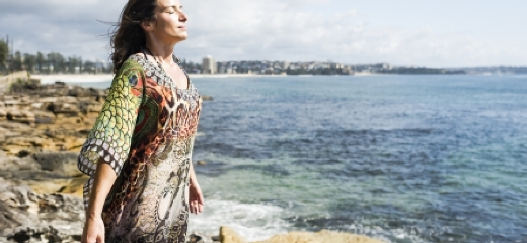 woman standing at the ocean shore arms open eyes closed breathing