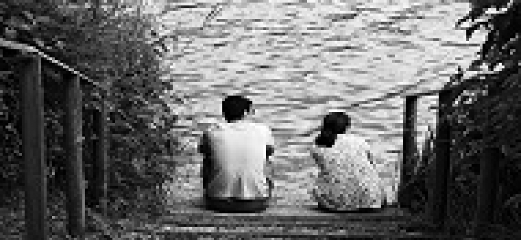 man and woman with backs turned sitting at a lake