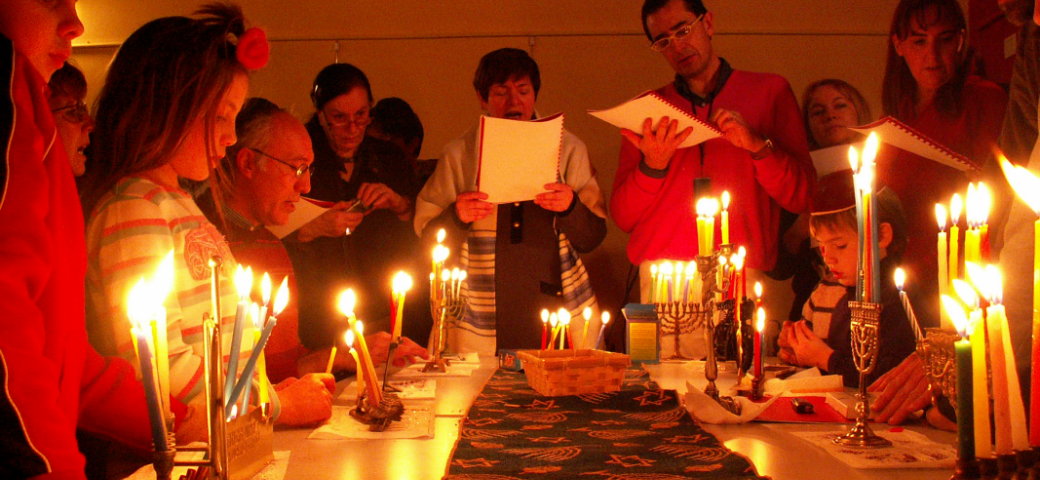 group of people singing around many hanukkah menorahs lit with candles