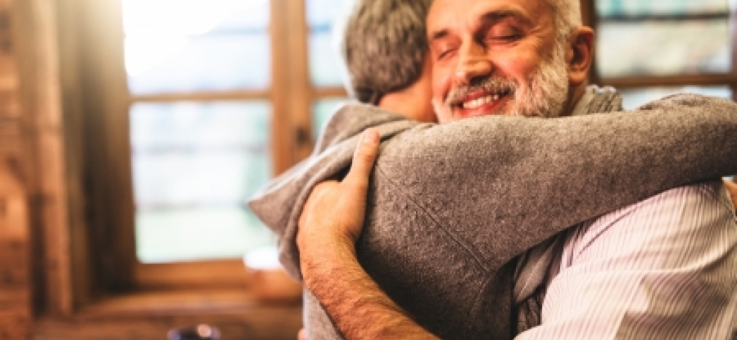 Bearded man smiling and embracing friend or partner