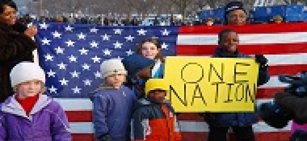 diverse people holding an american flag with one child holding a sign that says One Nation