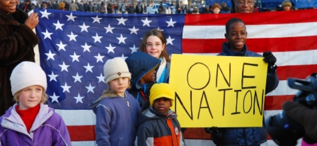 "three Black children, three white children and two Black adults are posing. One of the Black boys is holding a protest sign that says ""one nation"" while the adults in the background hold an American flag."