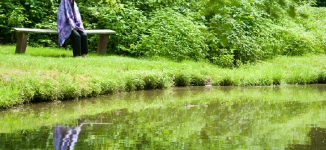Person wrapped in purple tallit sitting on a bench meditating before their own reflection in a lake