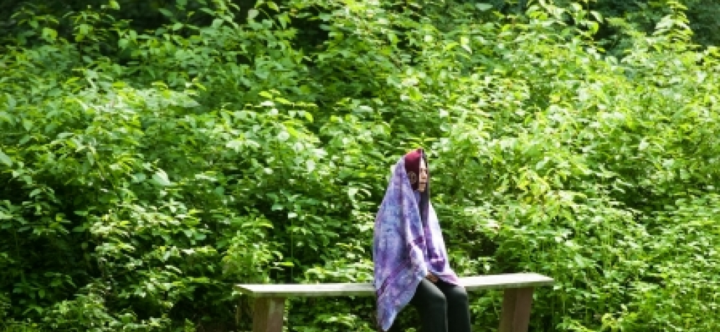 Person wrapped in purple tallit sitting on a bench surrounded by trees