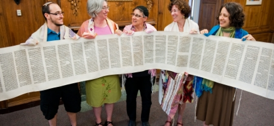 group of people holding unscrolled torah