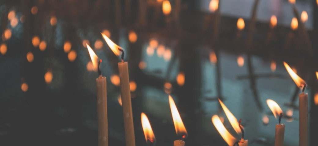 several lit candles with other lit candles blurred in the background