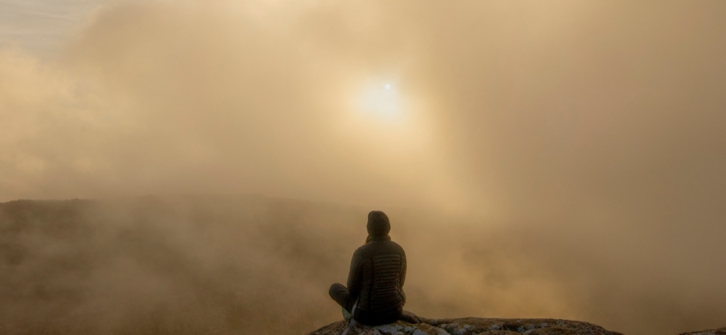 person sitting on large rock/mountain with misty gray clouds all around and sun shining through