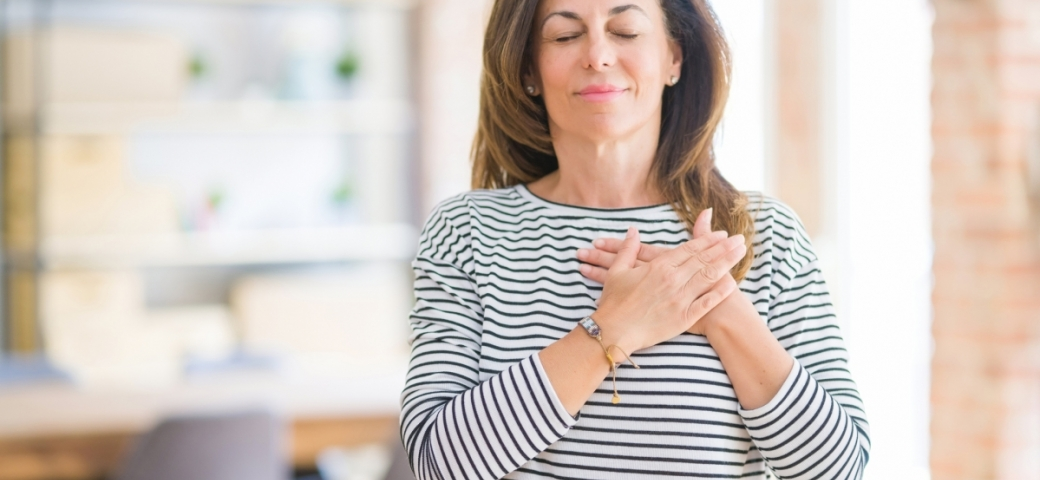 middle aged woman standing in brightly lit room with eyes closed, slight smile, and her two hands placed on her heart