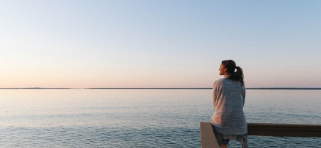 woman sitting on deck looking wistfully out to the ocean