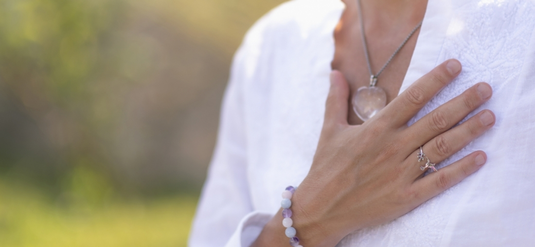 a person in a white linen shirt has their hand on their heart. They have on a silver ring, a silver chain necklace with a big pink gem in the middle and a bracelet made of blue and white and purple beads.