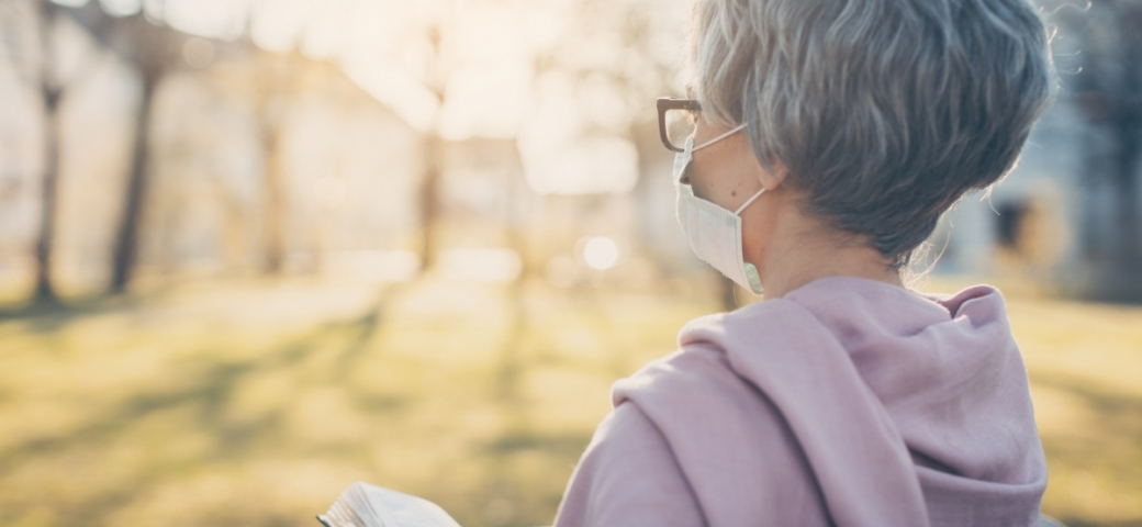 woman with short gray hair standing outside in sunlight wearing mask and holding book