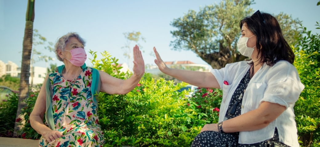 old woman in flowery dress sitting outside on a clear day wearing a pink mask holding out her hand for a high five as another woman who may be a nurse wearing a mask holds her hand out for a high five. there hands are not touching but they are looking at each other and smiling.