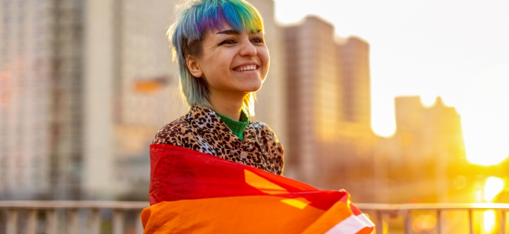 gender fluid person smiling in sunny city scene with brightly colored hair wrapped in rainbow flag