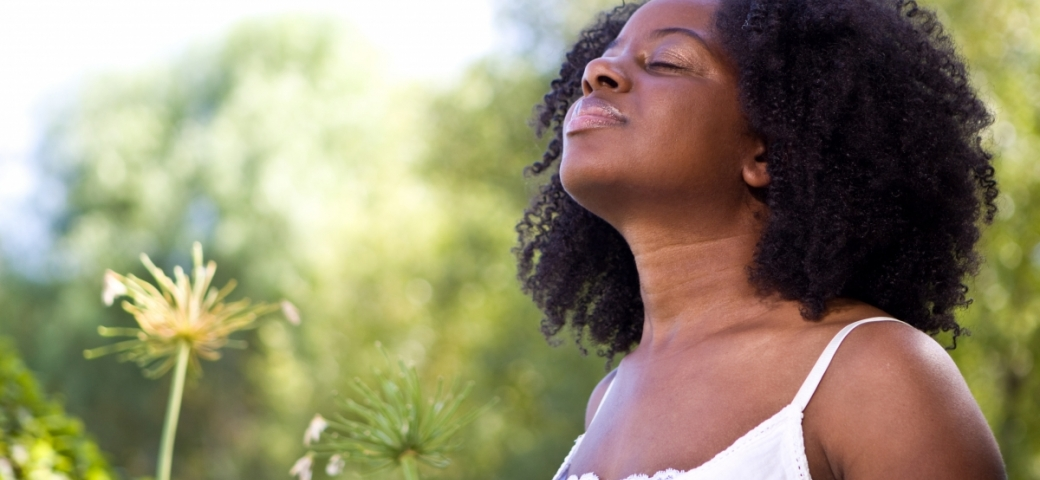 a black woman with curly dark hair has her eyes closed and chin up towards the sky. She is standing in front of a background of green nature