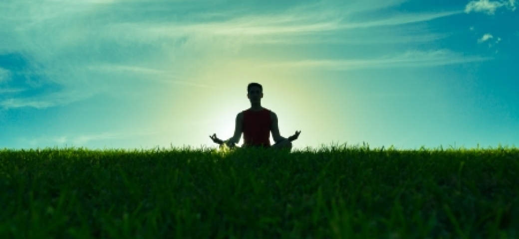 person meditating in a field