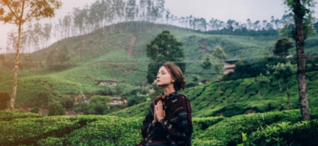 woman meditating in green mountains