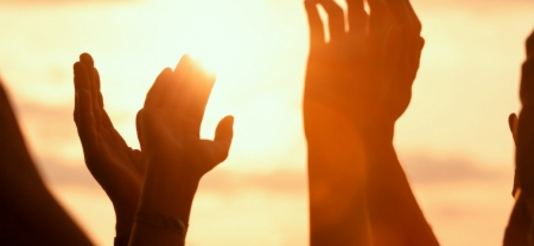 hands lifted up to sunlit sky