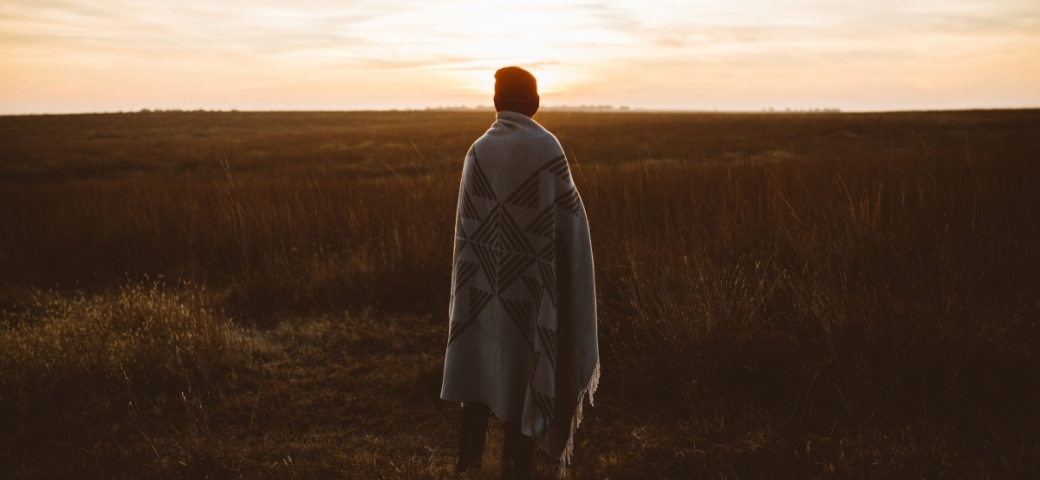 person shown from behind in field with blanket wrapped around them and knitted hat on looking out at sunlit sky