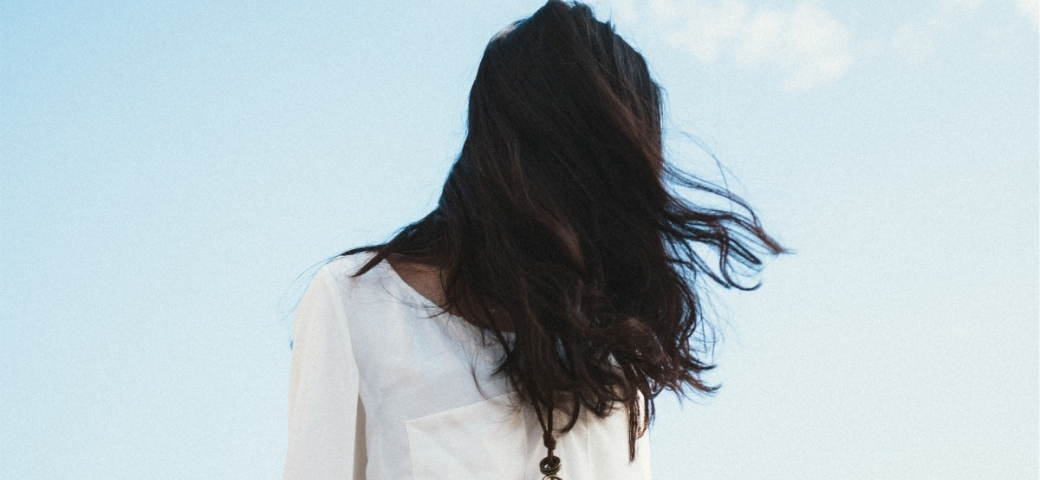 woman in white shirt with light skin and dark hair blowing across her face and covering her face wearing a necklace with a key in front of a blue open sky