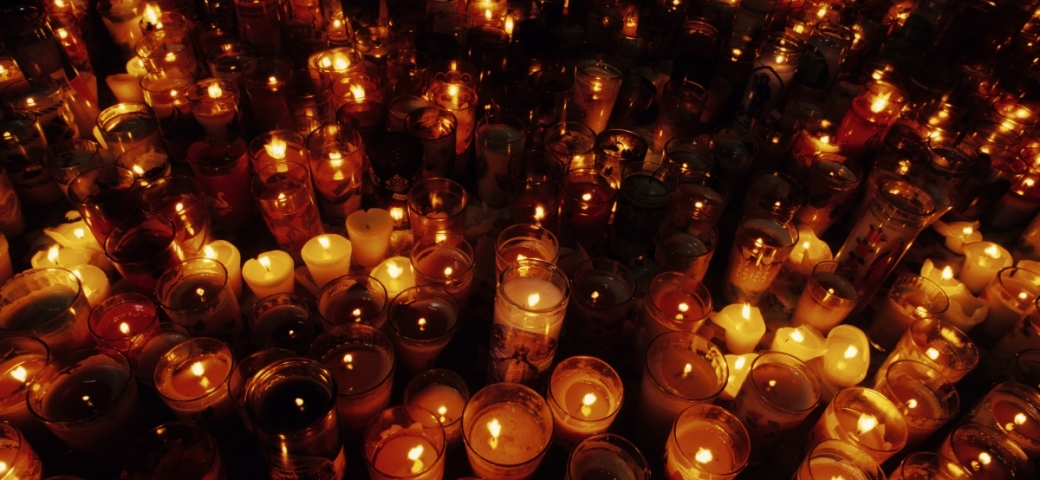 dozens of lit memorial candles fill the image. The flames create an orange/yellow hue to an otherwise dark image.