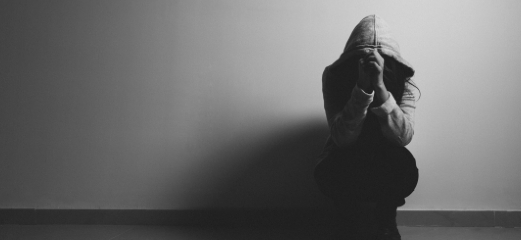 black and white photo of person with hood on crouched in front of a wall