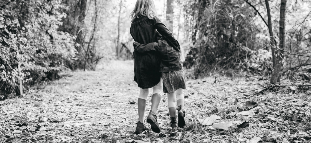 black and white photo of two children walking in forest hugging