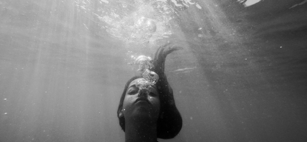 black and white photo of woman with eyes closed underwater bubbles around her mouth