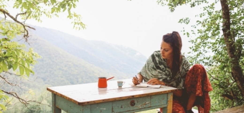 woman writing in journal outdoors at desk