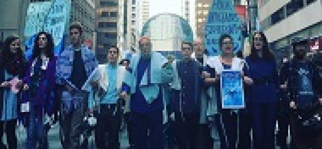 """people walking arm and arm on a busy street downtown; holding signs saying """"water is life"""""""