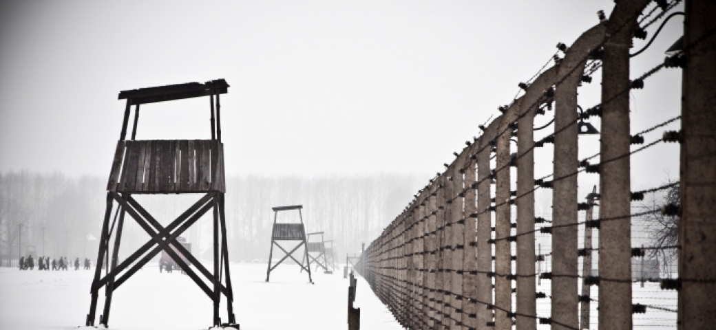 photo of guard tower and barbed fence in concentration camp