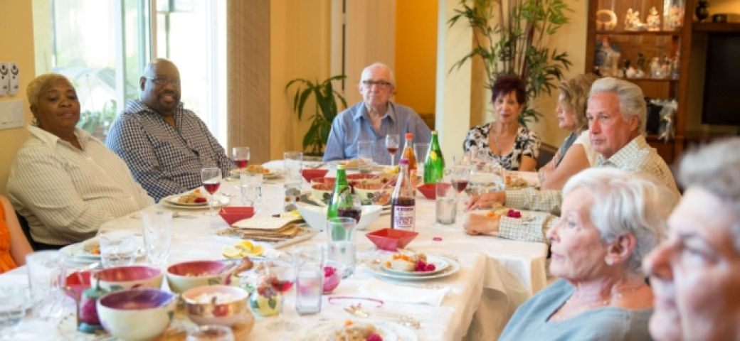 multicultural adults sitting around table with wine