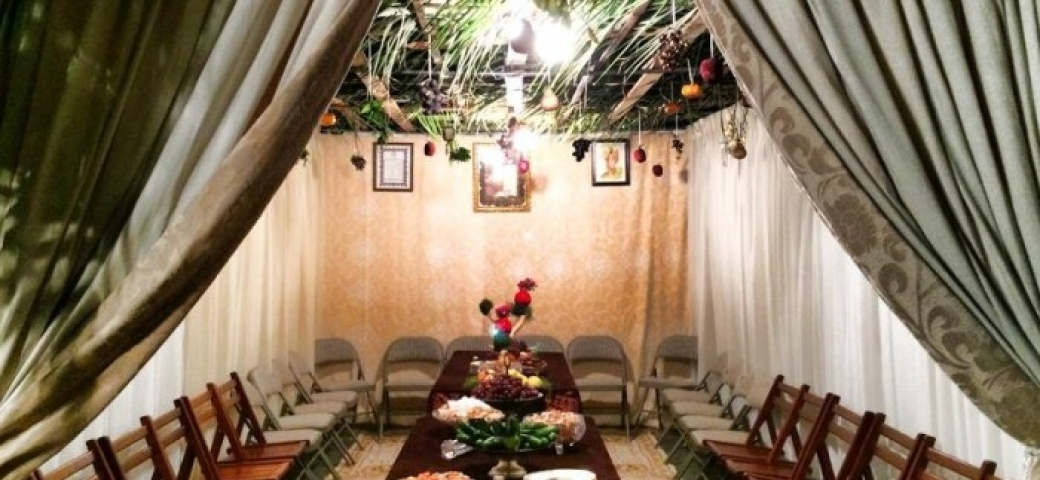 beautiful table in a sukkah, framed by curtains
