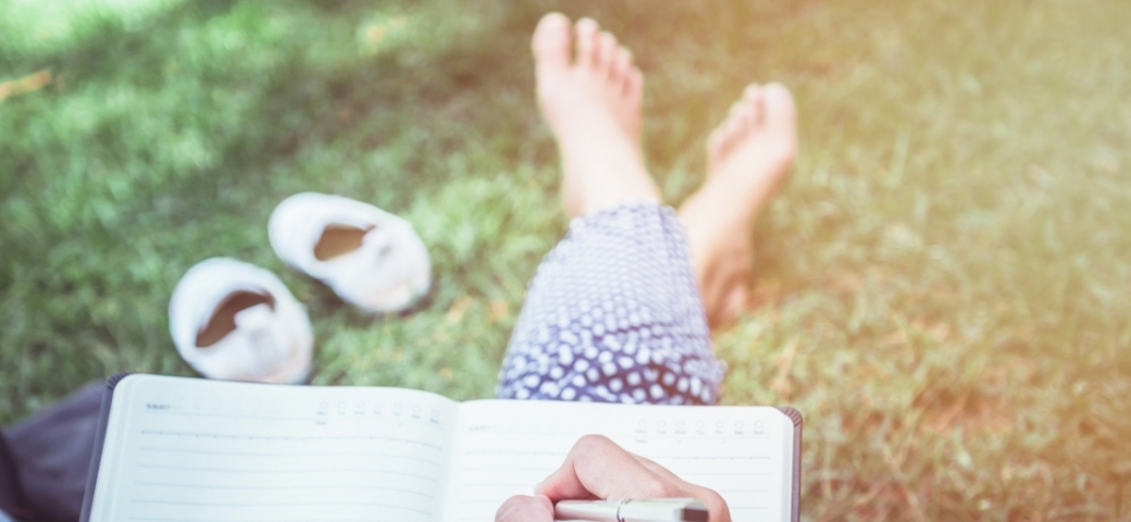 person sitting on grass outside writing in journal