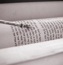 yad (pointer) pointing to a page of Torah