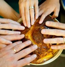 hands touching round challah