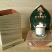 yizkor box and candle with emerald backplate in the shape of a flame