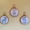 three embroidery circles with creatures sewn in each circle with different hebrew words sewn in their bellies