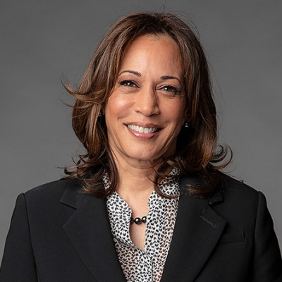 Vice President Kamala Harris is pictured in a black blazer and black and white top in front of a grey background