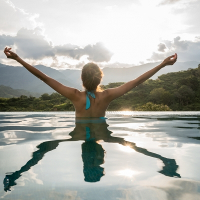 woman emerging from lake with arms to the sunny sky