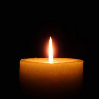 a single candle is lit against a dark background creating an orange glow