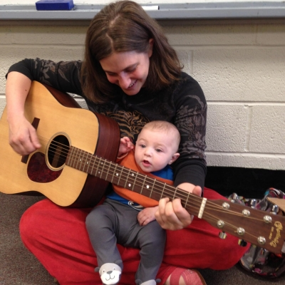 chana rothman playing guitar with one of her sons