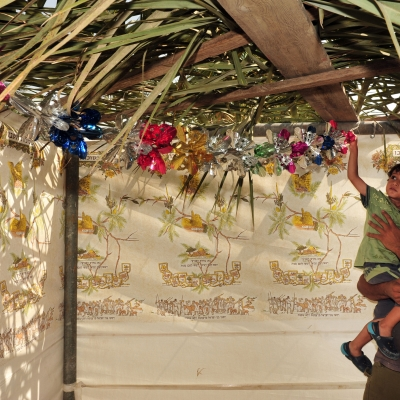 smiling brown-skinned man holding child up to touch the colorful decorations on the roof of a sukkah