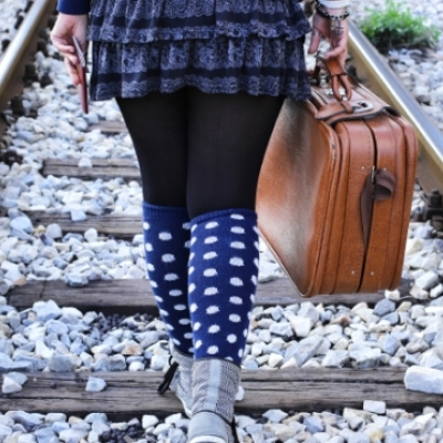 woman walking on train tracks with suitcase in hand