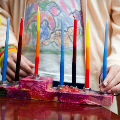 girl standing behind hanukkiah with unlit candles