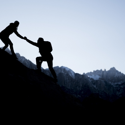 one person helping another climb a mountain