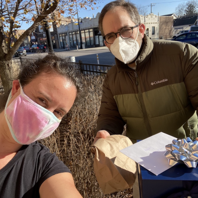 Ritualwell editor and neighbor wearing masks, standing outside, exchanging hanukkah food packages