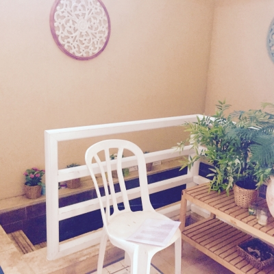 mikveh room with white railing, white chair, and potted plants