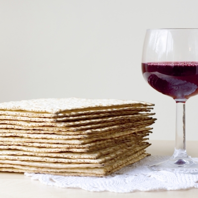 a stack of matzah sits on a plate next to a full glass of red wine