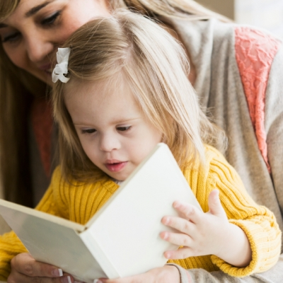 mother reading to daughter with downs syndrome